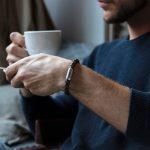 Mann hält Kaffeetasse und traegt Lederarmband mit graviertem Magnetverschluss silber von Fischers Fritze