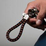 Hand haelt Schluesselanhaenger Segeltau marineblau orange, Edelstahlfassung mit Gravur sichtbar