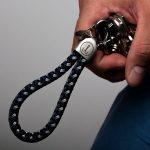 Hand haelt Schluesselanhaenger Segeltau marineblau grau, Edelstahlfassung mit Gravur sichtbar