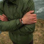 Mann steht auf Felsen an Kueste, trägt Armband marineblau braun mit Edelstahl Gravur von Fischers Fritze, aus Segeltau