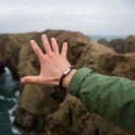 Ausgestreckte Hand Richtung Meer, mit Armband Makrele Segeltau von Fischers Fritze