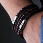 close-up magnetic clasp silver bracelet leather black braided and sail rope navy blue orange at wrist of Fischers Fritze