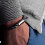 Um Handgelenk gelegtes Segeltau-Armband von Fischers Fritze, Makrele grau gedreht mit Angelhaken-Gravur, Hand in Hosentasche