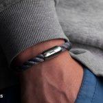 Um Handgelenk gelegtes Segeltau-Armband von Fischers Fritze, Makrele grau gedreht, Angelhaken-Gravur