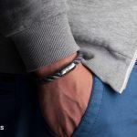 Um Handgelenk gelegtes Segeltau-Armband von Fischers Fritze, Makrele grau gedreht, Angelhaken-Gravur, Hand in Hosentasche