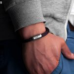Bracelet made of sail rope with engraving by Fischers Fritze on wrist, Mackerelnavy blue dark red, hand in trouser pocket