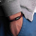 Handgelenk mit dunkelrotem Fischers Fritze-Armband, Torpedomakrele Magnetverschluss schwarz mit Edelstahl-Gravur