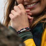Junge Frau lächelt, traegt ein Segeltau Wickelarmband von Fischers Fritze in marineblau rot weiss