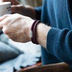 Mann hält Kaffeetasse und traegt Segeltauarmband mit graviertem Magnetverschluss silber von Fischers Fritze