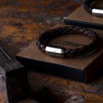 Armband Leder braun geflochten und Geschenkkarton liegen auf Werkbank in der Fischers Fritze-Werkstatt