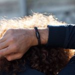 Arm hinter Kopf, Fischers Fritze Armband angelegt, Torpedomakrele aus Segeltau dunkelrot schwarz, Gravur sichtbar