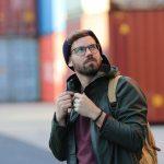 Hip gekleideter, junger Mann spaziert zwischen Frachtcontainer, er traegt ein Fischers Fritze Armband am Handgelenk